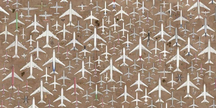dozens of airplanes and aircrafts (from above and pointing north) forming geometric patterns over a desert