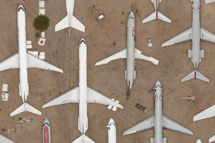 Several airplanes and aircrafts from above forming geometric patterns over a desert